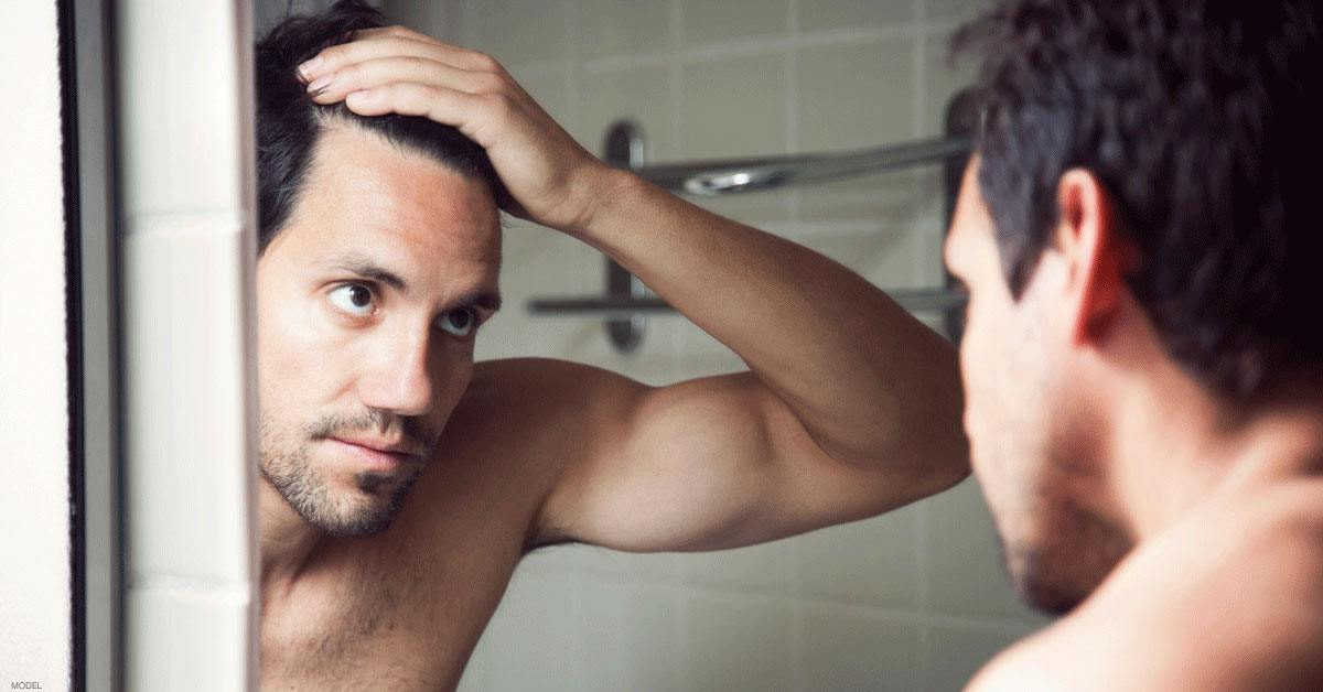Man touching his hair looking mirror